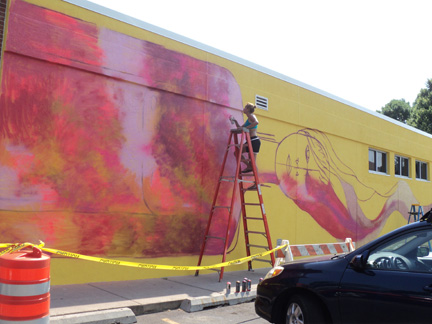 Panmela Castro painting a mural on Willy East